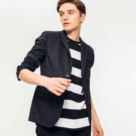ラコステ(LACOSTE)のシアサッカーテーラードジャケット。都会的な佇まいを演出する2ボタン仕様のテーラードジャケット。そんな大人顔なアイテムに、薄手仕立ての軽量シアサッカー素材を採用。表面に現れる独特の凹凸形状で、サラッとドライなタッチ感を演出するシーズナルな1着です。バックにはセンターベントデザインを採用しています。[型番:VH735EL]